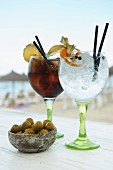 A gin and tonic and a rum and coke with a little bowl of olives in the 'Ponderosa' bar in Mallorca, Spain