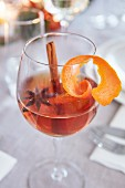 A wine glass of punch with star anise, a cinnamon stick and orange peel