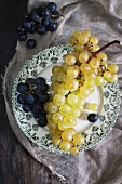 Purple and green grapes on a plate (seen from above)