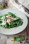 Vegan spinach salad with a garlic dressing, pine nuts and edible flowers