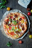 Homemade pizza topped with colourful cherry tomatoes, mozzarella and gorgonzola