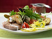 Grilled tuna with roasted potatoes, served with a mixed leaf salad and a pepper dressing