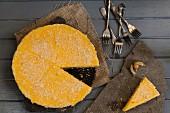 Zitronen-Käsekuchen, angeschnitten, Gabeln und Physalis