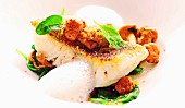 Pike-perch on a bed of spinach and chanterelles