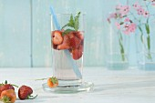 Water flavoured with strawberries and peppermint in a glass with a straw