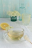 Elderflower tea in a cup, elderflowers, lemon and a rock candy stick