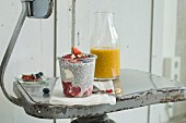 A chia pudding with summer fruits and nuts in a glass and a mango and orange smoothie with chia seeds on an old chair