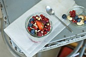 Chia pudding with summer fruits and nuts in a glass on an old chair