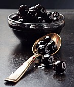 Black olives in a glass bowl and on a spoon