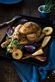 A whole roast chicken with parsnips, roasted onions and apples