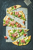 Fig, prosciutto, arugula and sage flatbread pizza cut into pieces on baking paper
