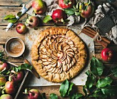 Apple crostata pie with cinnamon served with fresh garden apples with leaves on rustic wooden background