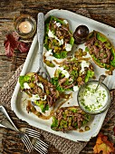 Baked potato skins, filled with spicy minted lamb shoulder and lettuce