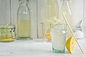 Holunderblütengetränk im Glas mit Trinkhalm und selbstgemachter Holunderblütensirup in Flaschen