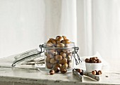 Hazelnuts in and next to a glass jar and a nutcracker on a rustic kitchen table