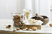 Almonds in and next to a glass jar and a nutcracker on a rustic kitchen table