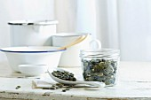Pumpkin seeds in a glass jar and on a spoon on a rustic kitchen table
