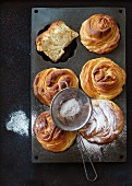 Fresh baked modern pastries cruffins, with sugar powder served in silicon baking form with sieve