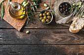 Olivenöl, Olivenzweige, grüne und schwarze Oliven in Blechdosen und Brotscheibe