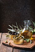 Green and black olives in tin cans, young olives branch and bottle of olive oil on clay board
