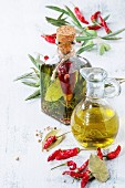 Glass bottle and jug of spicy olive oil with rosemary, red hot chili peppers and bay leaf