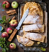 Sliced homemade apple strudel served with fresh apples with leaves, cinnamon sticks and sugar powder