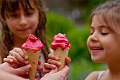 Zwei Mädchen essen Waffelhörnchen mit Erdbeersorbet