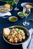 Lemon Feta Roasted Potatoes with roasted red peppers and parsley served with bread and white wine