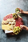 Cheese board with assorted sausages and salami, fresh fruit and various cheeses, female hand reaching salami from a platter