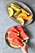 Fresh sliced melons on plates, female hands holding a slice of watermelon