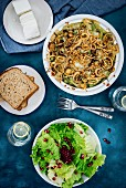 Skinny green bean casserole with mushroom served with a bowl of salad, bread and cheese