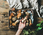 Fresh picked Porcini mushrooms in wooden tray over rustic background