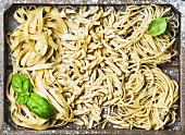 Verschiedene hausgemachte, italienische Nudelsorten mit Mehl und Basilikumblättern auf Holztablett