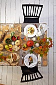 Autumnal dining table decorated with pumpkins and leaves