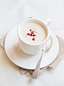 Cup of cauliflower cream soup served with pomegranate