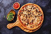 Pizza with mushrooms on wood olive cutting board on dark background