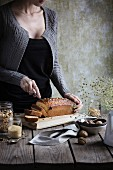 Frau schneidet Müsli-Kuchen auf einem rustikalen Holztisch