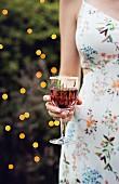 Frau in Sommerkleid hält Blackberry-Cocktail in der Hand