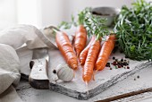 Fresh carrots with garlic and pepper on a chopping board