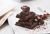 Stacked pieces of chocolate with cocoa powder on a chopping board