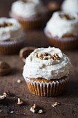 Pumpkin cupcake with cream cheese frosting and walnuts.