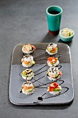 Eight mini sushi burgers on a ceramic plate with smoked and fresh salmon, surimi and shrimp