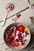 A breakfast of porridge with strawberry compote and fresh edible flowers (seen from above)