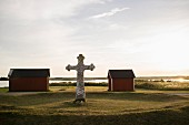 The stone cross of Kapelludden with wooden huts in the background on the island of Öland in southern Sweden