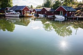 Motorboats in front of wooden huts by a lake in southern Sweden