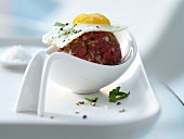 Beef stew in a spoon with a quail egg