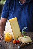 A man holding a cheese board with tomatoes and a jam jar