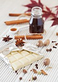 Stillleben mit weisser Schokolade, Gewürzen und Sirup