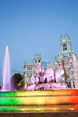 The Palacio de Cibeles with the colourfully illuminated Fuente de Cibeles fountain in Madrid, Spain