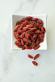 Goji berries in a white bowl on a marble background